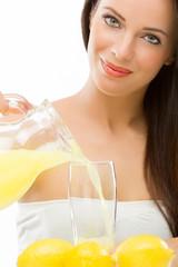 beautiful woman pouring lemon juice in a glass