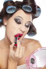 Funny woman with curlers and bad makeup applied lipstick