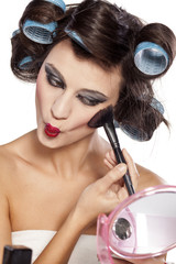 funny woman with curlers and bad makeup applied blush