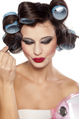 funny woman with curlers and bad makeup looking herself