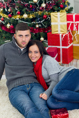young happy couple sitting on the floor next to the Christmas tr