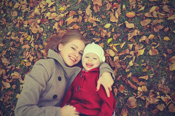 happy family: mother and child little daughter on autumn