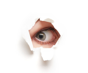 Eye looking through  hole in  white empty paper poster