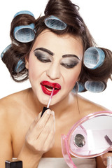 Funny woman with curlers and bad makeup applied lip gloss