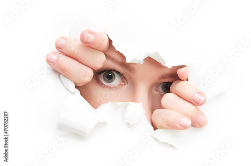 eyes of woman peeking through a  hole torn in white paper poster - 70782207