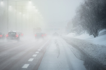 Road with traffic and heavy fog