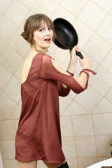 Angry attractive girl in evening dress holding a frying pan.