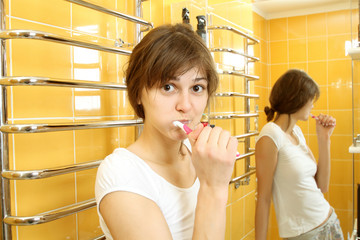 girl in a white shirt and shorts, brushing her teeth