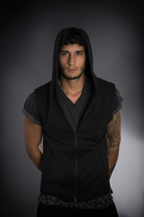 Handsome young man in dark hoodie on black