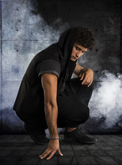 Handsome young man kneeling down in dark hoodie on black