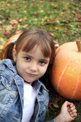 Autumn photo of a young girl with pumpkins