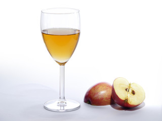 apple juice in a glass and sliced ??red apple, bright background