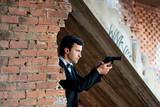 Man in tux holding a gun poster