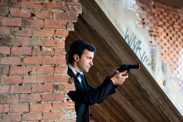 Man in tux holding a gun