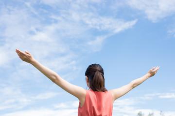 両腕を広げる女性と空