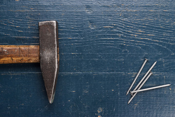 old hammer and nails on blue table