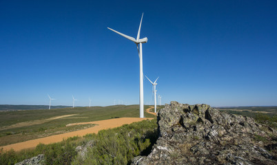 Wind turbines, track and rocks in the countryside