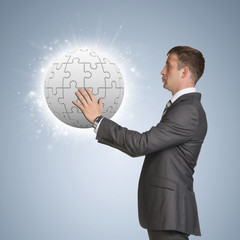 Businessman in suit hold jigsaw puzzle sphere