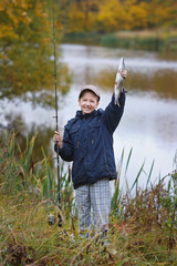 Boy with a fish and a fishing rod