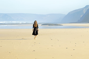 Lonely woman walking at the beach