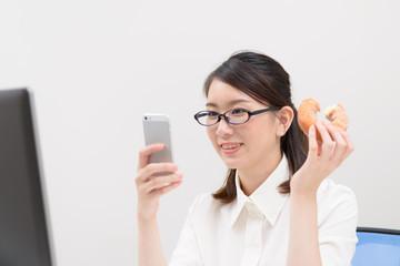 ドーナツを食べながらスマートフォンを見る女性