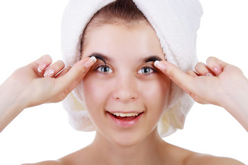 girl in a towel with braces, trying on eyelashes