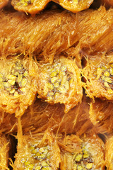 Turkish sweet baklava with honey and pistachios, selective focus