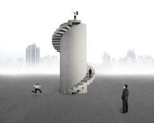 businessman watching men with concrete spiral tower