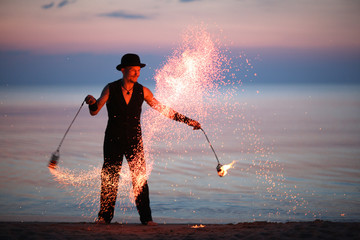 Showman spinning fire poi, sparks of fire