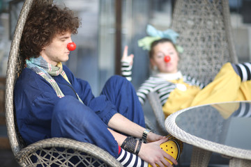 Clowns having rest in the cafe wicker chair