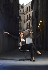 Happy Business woman on Office Chair on Street with Laptop