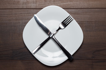 dieting concept white plate with knife and fork crossed