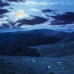 stones on the hillside of mountain range in full moon light