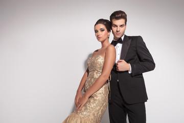fashion couple posing against studio background