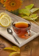 glass cup with tea on a tray with autumn leaves and flowers