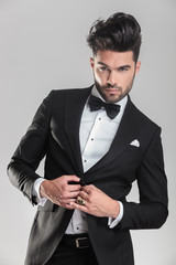 elegant man in tuxedo closing his jacket