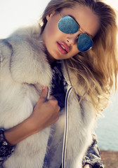 sexy woman with blond hair in fur coat and sunglasse