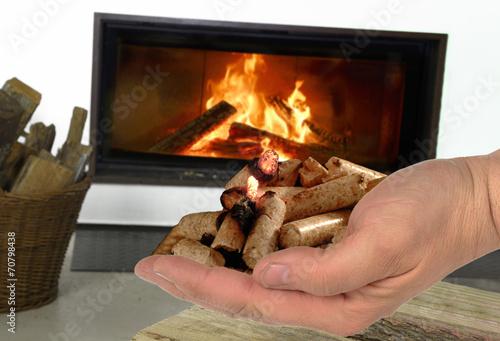 Hand mit brennenden Holzpellets vor Kamin
