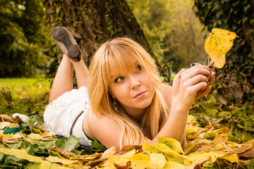 young woman lying on colorful autumn leaves in a park