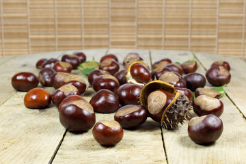 Chestnuts from an Autumn Harvest on an Old Wooden Table