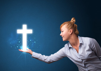 Glowing cross in the hand of a businesswoman