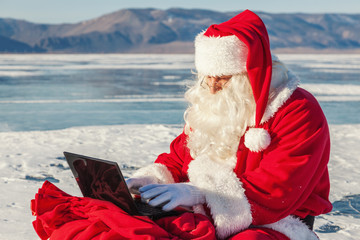 Santa Claus sitting on snow, looking at laptop news
