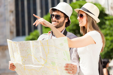 Happy tourists couple holding a map