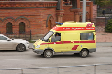 Yellow ambulance truck racing down the street in Russia