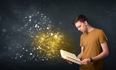 Young guy reading a magical book