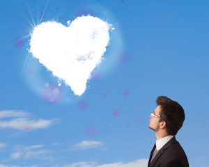 Handsome man looking at white heart cloud on blue sky