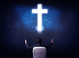 Businessman in chair with cross above his head
