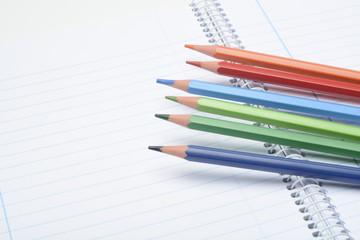 Lapices de colores y cuaderno abierto