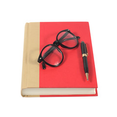 Red book with glasses and pen isolated on white background
