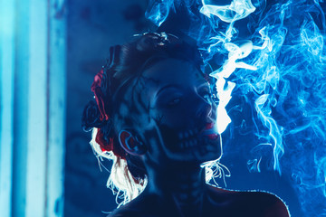 Face art of skull on woman face with smoke